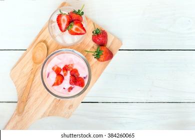 frische Saft-Erdbeere mit Jogurt in einer Glasschüssel und frische Erdbeere auf Eis auf Holzplattereis ; Draufsicht