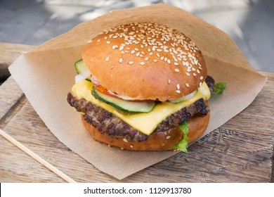 Fresh juicy tasty burger with beef on wooden table in craft paper.