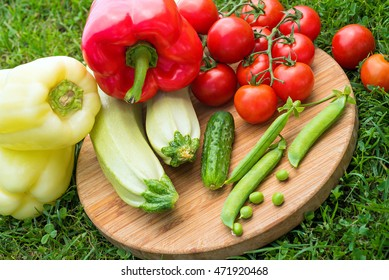 Fresh juicy vegetables on the wooden board on green grass. Top view. Tomato, cucumber, squash, green peas, sweet pepper on the wooden round board on sunny day. Close up. Healthy life concept.
