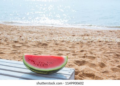 Fresh juicy watermelon on a background of a sandy beach and the sea.