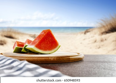 Fresh juicy watermelon on desk and background of beach with sea and blue sky