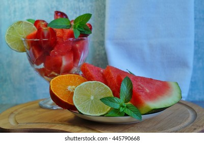 Fresh and juicy watermelon sliced on a white plate and diced glass dish - selective focus
