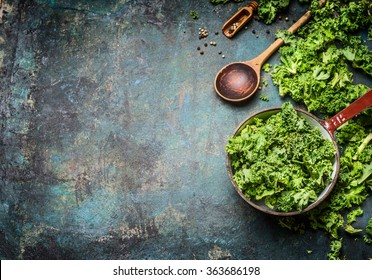 Fresh kale in cooking pot with wooden spoon on  rustic background, top view, border. Healthy food or diet nutrition concept.