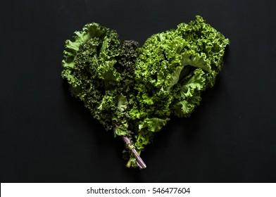 Fresh kale leaf vegetable on black background. Heart-shaped. Go green