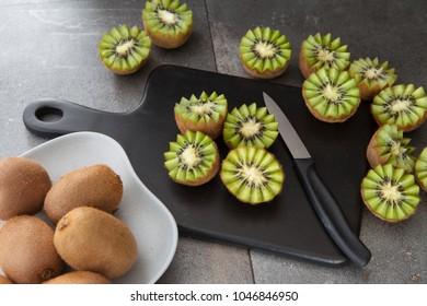 Fresh kiwi fruits on a dark stone background