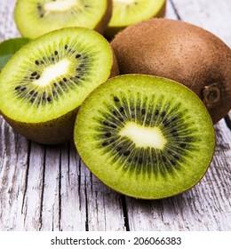Fresh kiwi fruits on wooden table. Wood background.