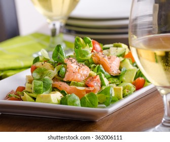 Fresh lamb lettuce salad with avocado, cucumber, salmon, cherry tomatoes. Dressing with honey, dijon mustard, olive oil and lemon juice, topped with chia seeds. Prepared by chef