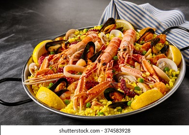Fresh langoustines in a seafood Valencia paella with clams, mussels and octopus on a bed of saffron rice garnished with lemon slices in a gourmet presentation
