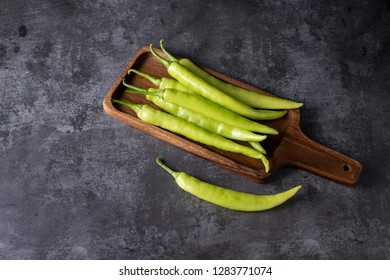 Fresh large green chilli on dark textured background, young pepper chilli with copy space