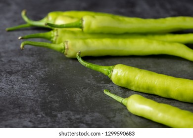 Fresh large green chilli on dark textured background, young pepper chilli with selective focus