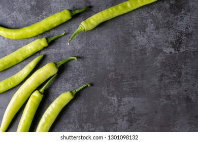 Fresh large green chilli on dark textured background, young pepper chilli, flat lay with copy space