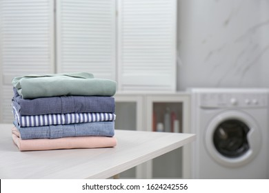 Fresh laundry on white wooden table in bathroom. Space for text