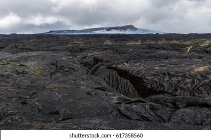 Fresh lava field with crevasse of recents flows from Kilauea's creater of Puu Oo, Big Island Hawaii. The cone of Puu Oo is visible in the background. New plants are already growing on the lava.