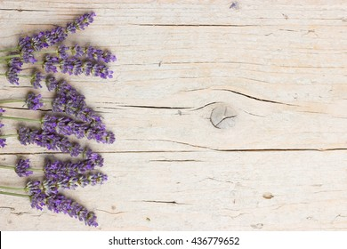 Fresh lavender flowers on wooden background. Lateral frame with space for text. Lovely postcard