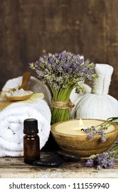 Fresh  lavender flowers, zen stones, essential oil, candle, Herbal massage balls  and towel over wooden surface