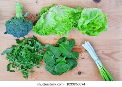 Fresh leafy vegetables, broccoli, lettuce, arugula, salad, spinach, scallions on wooden table