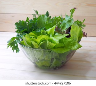 Fresh leaves of salad. Lettuce, spinach, arugula, celery, parsley on a wooden table. Organic vegetables from the garden. Healthy foods rich in vitamins