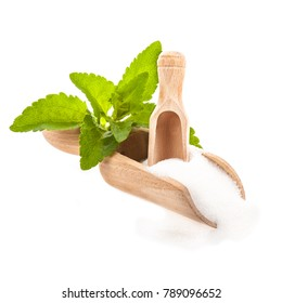 Fresh leaves of stevia, a wooden spoon and scattered sugar from stevia   close-up isolated on white background