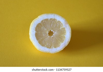 A fresh lemon cut in half on bright, neon yellow background texture