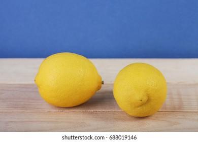 Fresh lemon fruit on wooden and blue background