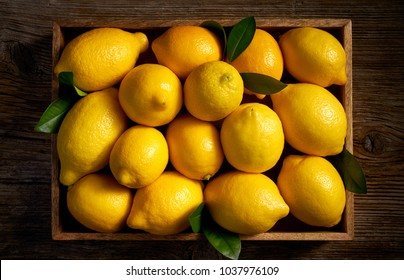 Fresh lemon fruits in a wooden box  on a wooden rustic table, top view