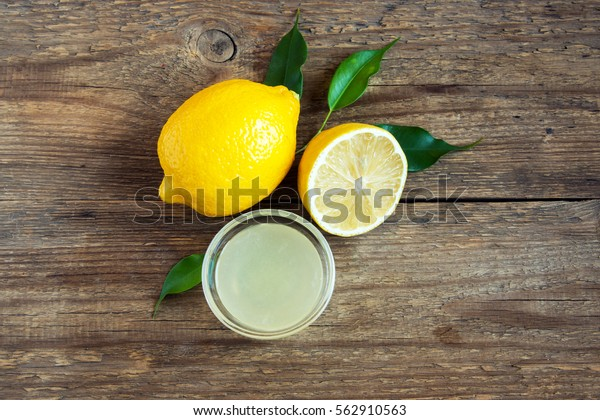 Fresh lemon juice in small bowl and lemons over rustic wooden background with copy space - healthy ingredient for cooking and baking