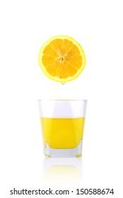 Fresh lemon over glass of lemon juice