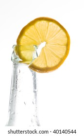 Fresh lemon slice decorates a bottle with a cold drink. Isolated on white with plenty of copy space.