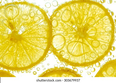 Fresh lemon slice in water with bubbles on white background