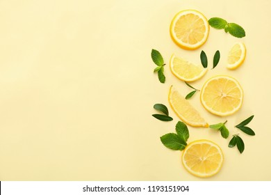 Fresh lemon slices and green leaves on color background, flat lay