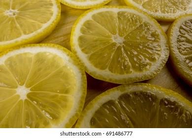Fresh lemon slices on the wooden background.
