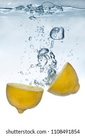 Fresh lemon splashing into clear fresh water.