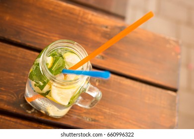 Fresh lemonade in a glass with a straw and a straw on the restaurant's terrace