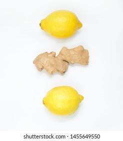 Fresh lemons and ginger root on a light background.