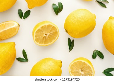 Fresh lemons and green leaves on white background, flat lay