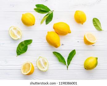 Fresh lemons and  lemons leaves on white wooden background.