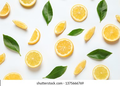 Fresh lemons and leaves on white background, top view. Citrus fruits