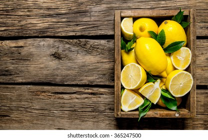 Fresh lemons in an old box with leaves. On wooden background. Free space for text . Top view