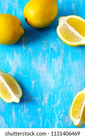 Fresh lemons on blue wooden background, frame, top view, copy space
