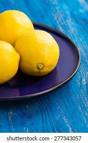 Fresh lemons on the blue wooden table