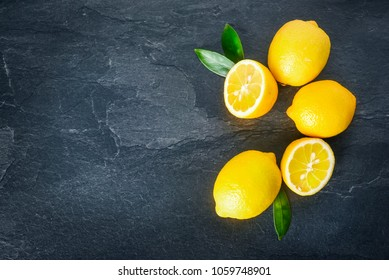 Fresh lemons on dark stone table. Ripe lemon from top view with green leaves. Fresh ripe lepon concept.