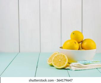 Fresh lemons in a white bowl on wooden background.Half of lemon.