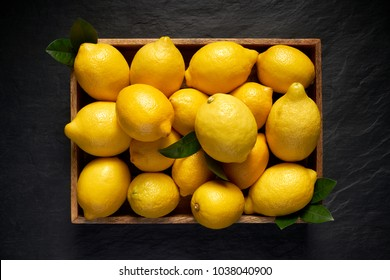 Fresh lemons in a wooden container on a black stone background, top view