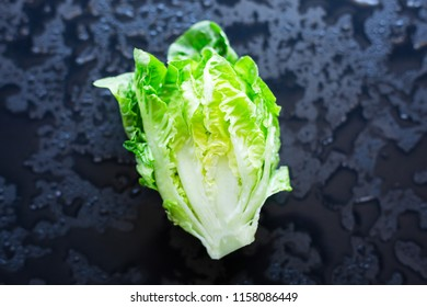 Fresh lettuce on a black background, cut in half, selective focus