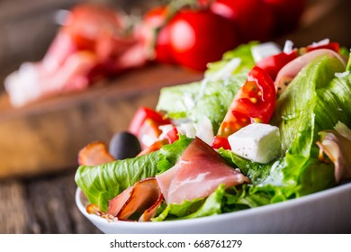 Fresh lettuce salad with olives tomatoes parmesan cheese and prosciutto.