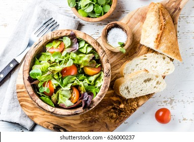 Fresh lettuce and tomatoes salad in olive wooden bowl. Top view. White wooden background