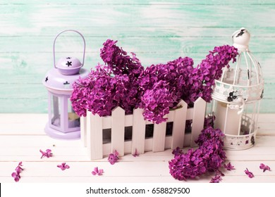 Fresh  lilac flowers in  bucket and lanterns on white wooden background against turquoise wall. Selective focus.