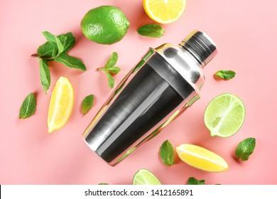 Fresh lime, lemon, shaker and mint leaves on color background