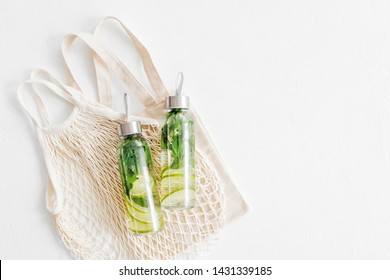 Fresh lime and mint infused water, cocktail, detox drink, lemonade in reusable bottles with eco bags. Eco friendly. Sustainable lifestyle.