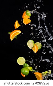 Fresh limes and oranges with water splashes isolated on black background